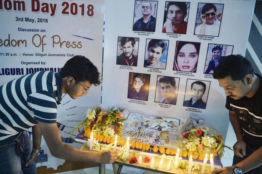 Indian journalists light candles during a vigil for ten Afghan journalists who were killed in a targeted suicide bombing during an event to mark World Press Freedom Day in Siliguri on May 3, 2018.