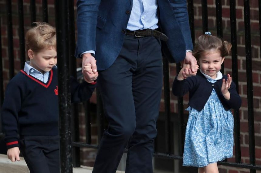 Princess Charlotte of Cambridge waves at the media as she is led in with her brother, Prince George of Cambridge, by their father, Britain's Prince William, Duke of Cambridge, at St Mary's Hospital in  London, on April 23, 2018.