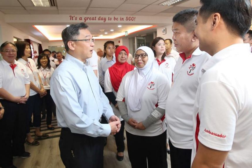 Minister for Health Gam Kim Yong speaking to Mdm Noraisah Yacob (second from left) and Mr Wong Kang Kheong Eddie (third from left) at the opening of the new Silver Generation Office Training Facility on May 4, 2018.