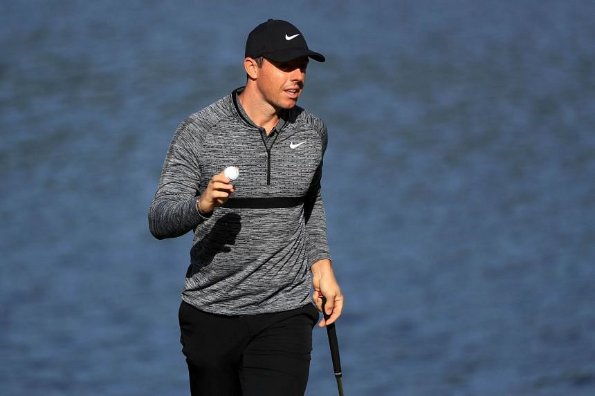 McIlroy acknowledges the gallery following his par putt attempt on the 14th green during the first round.