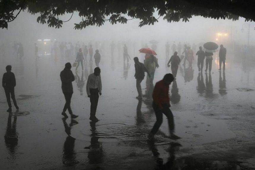 People walking under heavy rainfall in the northern hill town of Shimla in Himachal Pradesh state, on May 2, 2018.