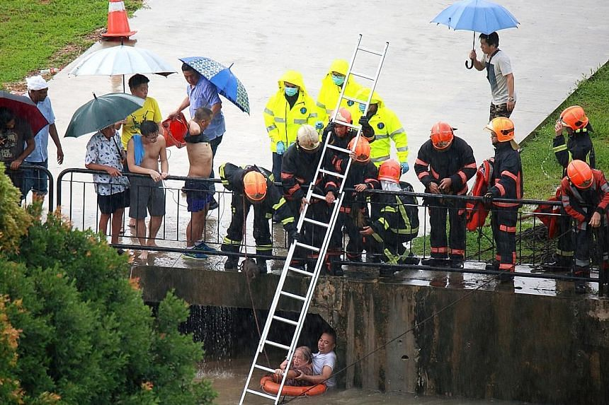 Two people were rescued from a flooded canal in MacPherson on Thursday after heavy rain. This photo by eye-witness Darren Colin Goh shows Singapore Civil Defence Force (SCDF) officers lowering a ladder into the canal in a bid to reach a man and a wom