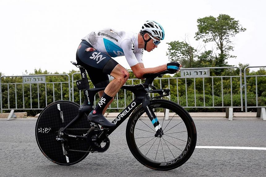 British rider Chris Froome pedalling on after crashing during reconnaissance of the 9.7km first-stage route of the Tour of Italy around Jerusalem yesterday. He received treatment and was cleared to race.