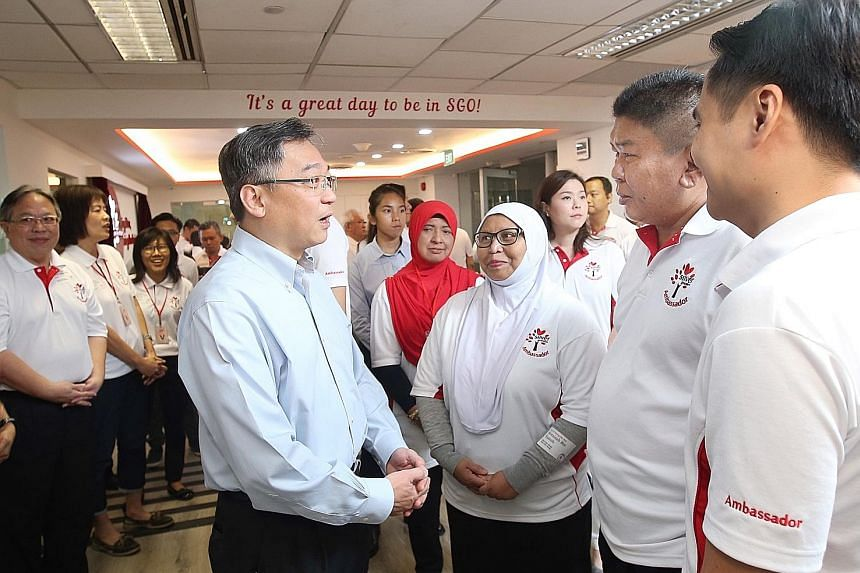 Health Minister Gan Kim Yong chatting with Madam Noraisah Yacob (third from right) and other volunteers at the official launch of the new Silver Generation Office training facility yesterday.