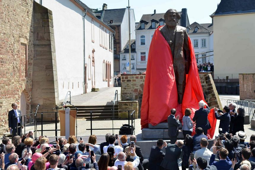 Visitors look on as a statue of German revolutionary thinker Karl Marx is unveiled in Trier.