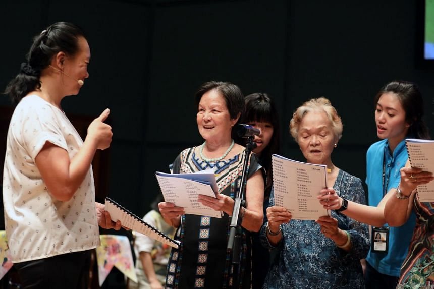 Vocal coach Angelina Choo (left) and participants of the Sing Out Loud! programme during their graduation showcase at the Esplanade.