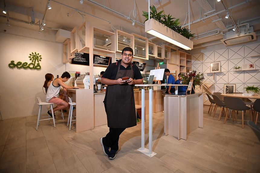Student in the Senior Programme at Rainbow Centre Harish Ganesan holding a Flat White Latte inside the cafe.