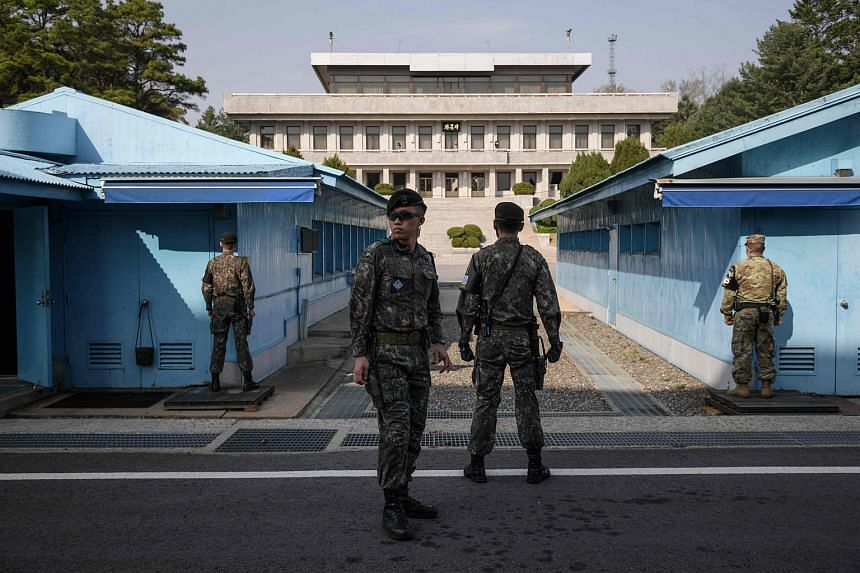 South Korean soldiers standing guard before a United Nations Command Military Armistice Commission (UNCMAC) meeting hut in the truce village of Panmunjom within the Demilitarized Zone (DMZ) separating North and South Korea.