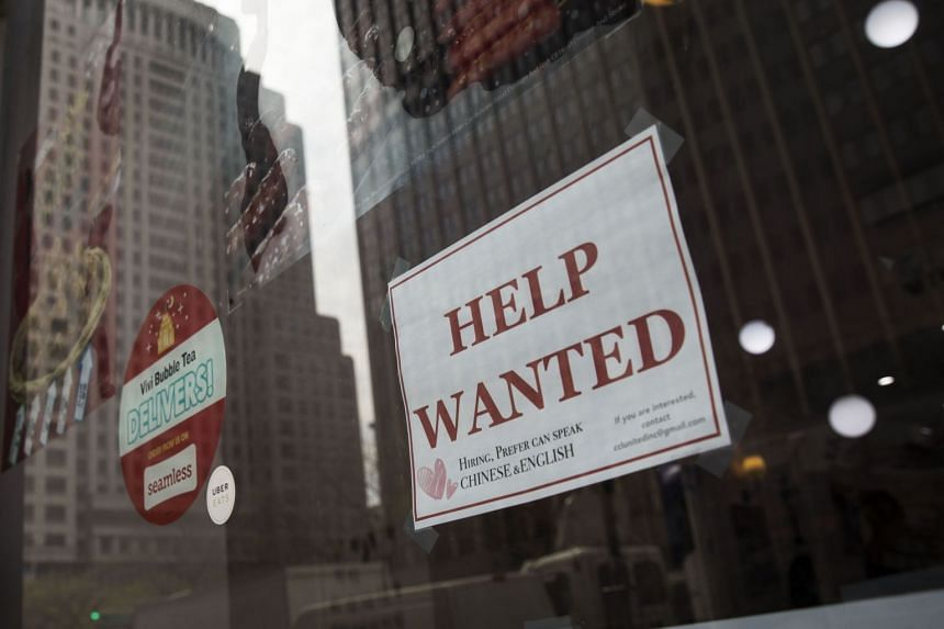 "A ""help wanted"" sign hangs on a window of a restaurant in Lower Manhattan, New York City, on May 4, 2018."