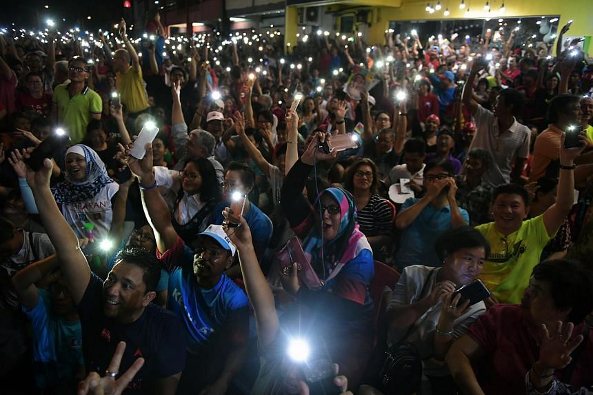 The crowd waving their mobile phone flashlights during the rally in Mutiara, Malacca.