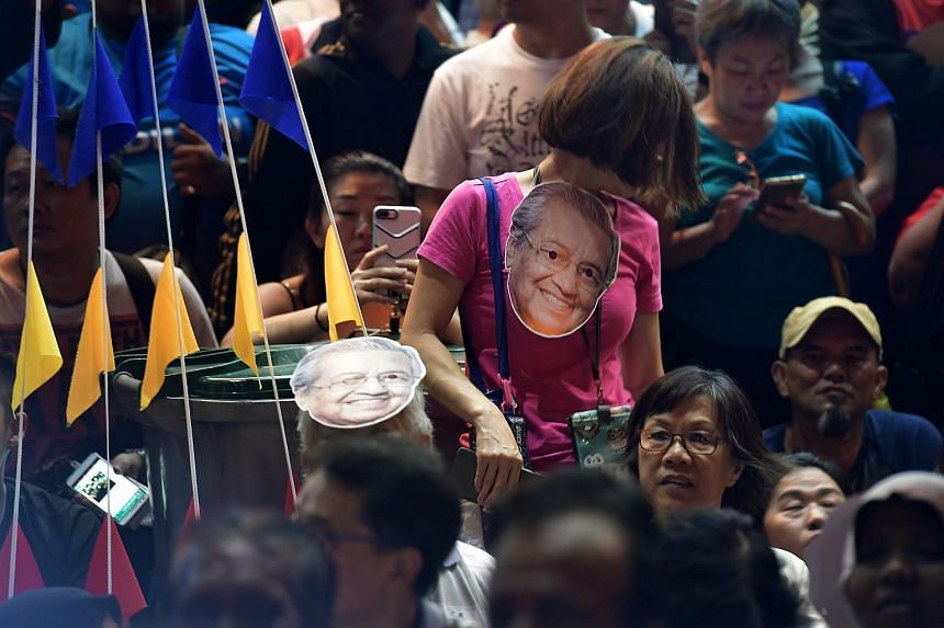 Members of the crowd seen with face masks of Mahathir Mohamad at the rally.
