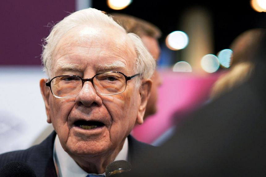 Buffett talks to a reporter in the exhibit hall at the company's annual meeting in Omaha, Nebraska.