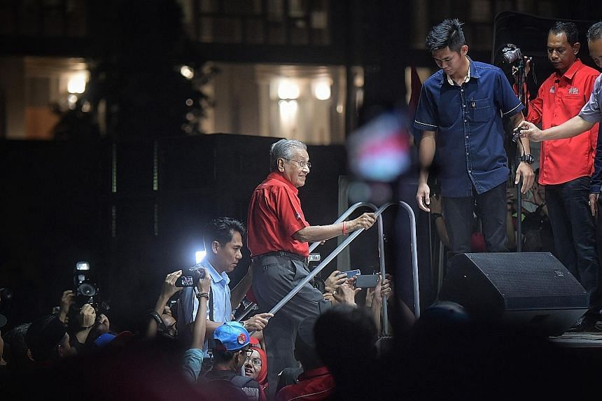 Tun Dr Mahathir Mohamad taking the stage at the Putrajaya rally on Thursday, where he aimed his message at the ward's largely civil servant population. Some came from as far as Subang Jaya 30km away to see him.