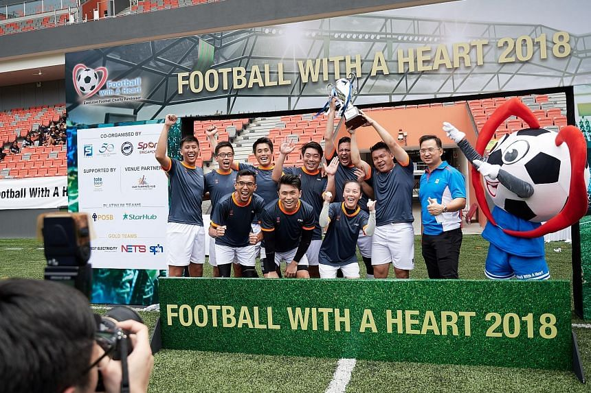 The winning team from PSA cheering as they lift the trophy. The fund-raiser drew 40 companies and more than 540 players.
