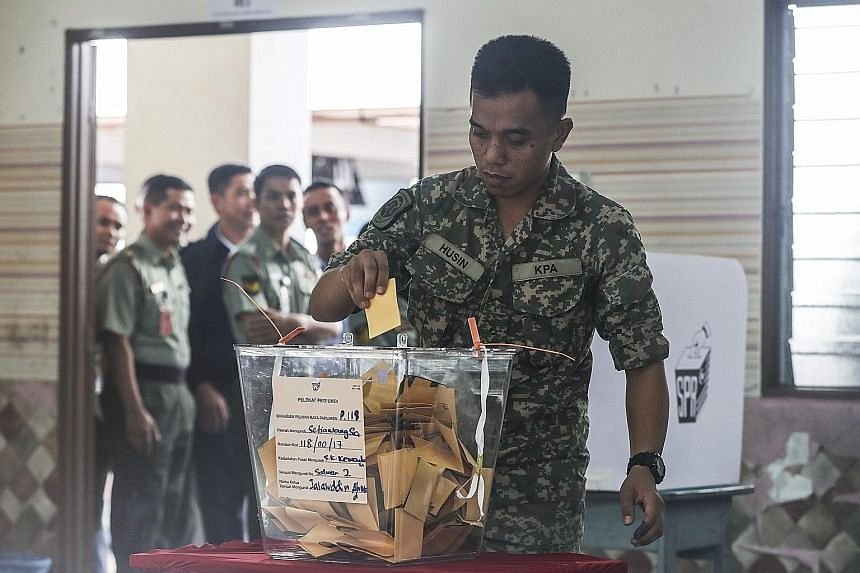 A Malaysian casting his ballot during early voting yesterday in Kuala Lumpur. Malaysia's federal Parliament has 222 seats. Winning a simple majority of 112 seats determines who forms the government.