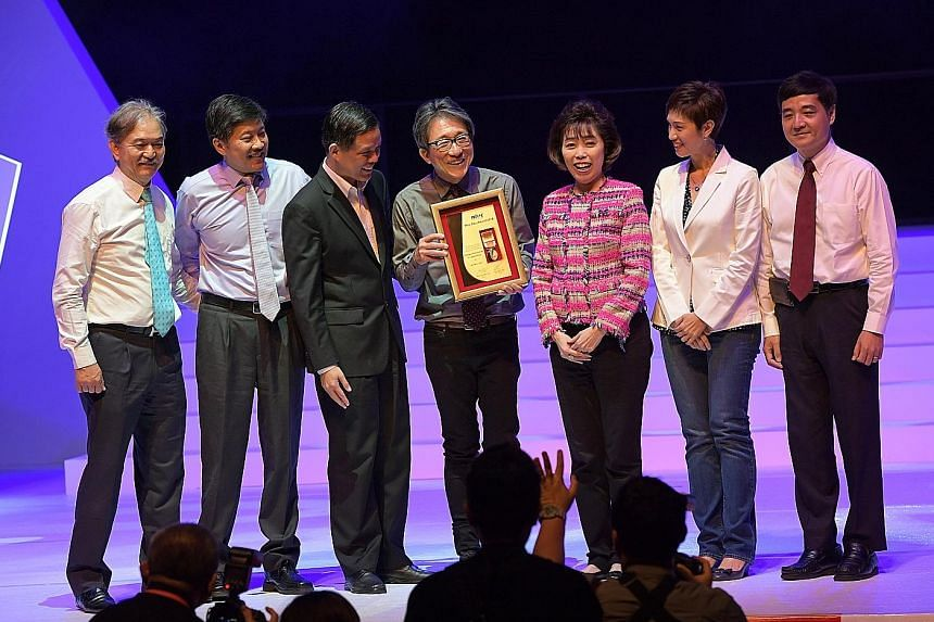 Former manpower minister Lim Swee Say with his Distinguished Comrade of Labour award at the May Day Awards ceremony yesterday. With him are (from left) Singapore National Employers Federation president Robert Yap, NTUC deputy secretary-general Ng Che