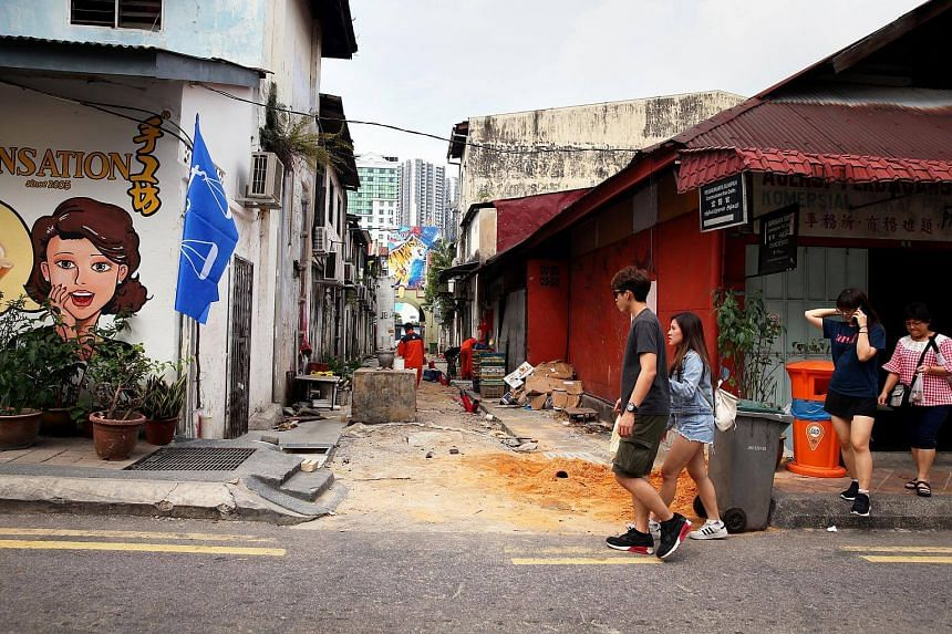 A backlane in Jalan Trus in Johor Baru being re-turfed as tourists walk past.