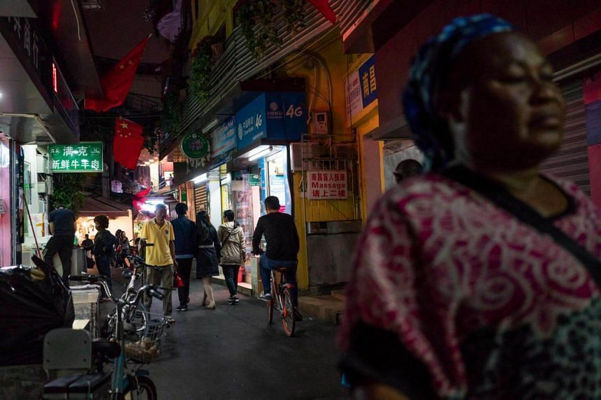 """People walking in the """"Little Africa"""" district of Guangzhou, the capital of southern China's Guangdong province, on March 1, 2018."""