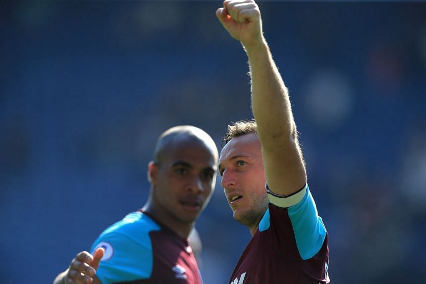 West Ham United's English midfielder Mark Noble (right) applauds the fans.