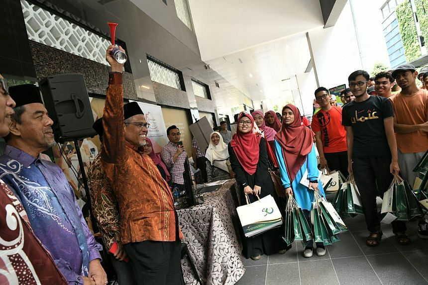 Minister in charge of Muslim Affairs Masagos Zulkifli (with airhorn) flagging off volunteers at Alfalah Mosque as part of the launch of the Senthuhan Ramadan campaign, on May 6, 2018.