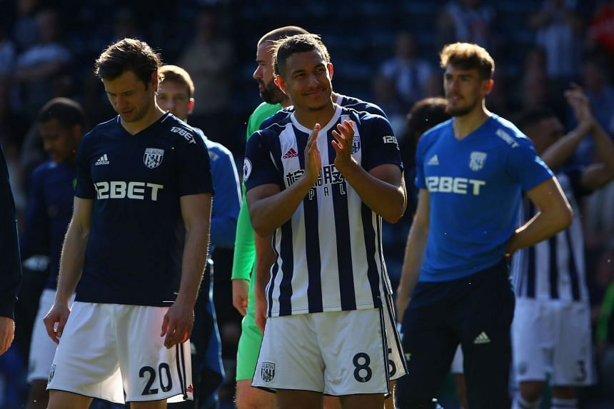 West Brom's English midfielder Jake Livermore (centre) applauds fans after the match.