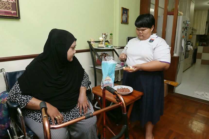 Nurul Syafiqah Roslan, 11, prepares breakfast for her mother, who has kidney failure, heart problems and uses a wheelchair.