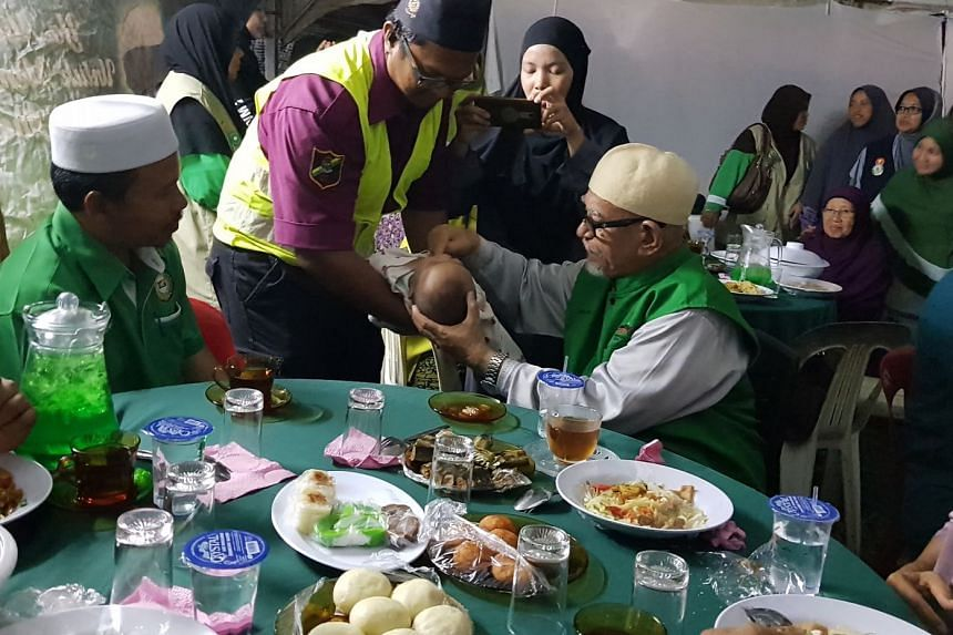 PAS president Abdul Hadi Awang feeding a a four-month-old baby a sweet mixture of dates and water from the Zamzam Well during his rally on Saturday in Alor Setar. He enjoyed strong support at the rally.