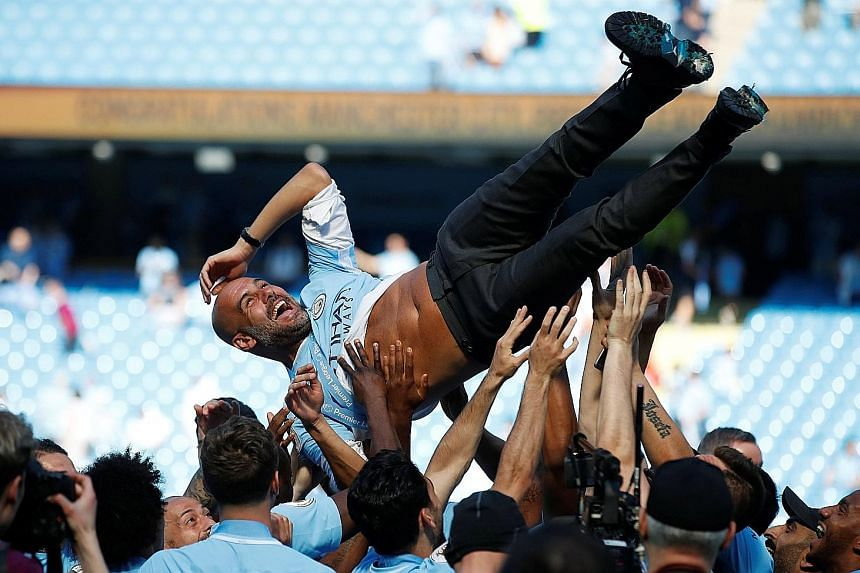 Manchester City manager Pep Guardiola being thrown into the air by his players after they were presented with the Premier League trophy at the Etihad Stadium, following a goalless draw with Huddersfield yesterday.
