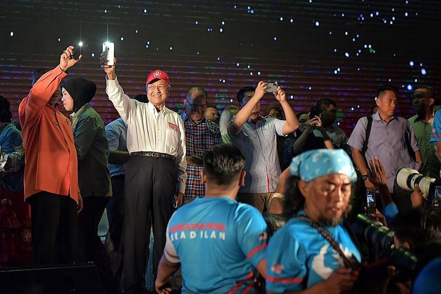 "Left: Tun Dr Mahathir Mohamad acknowledging the crowd of supporters at the mega ""ceramah"" or rally in Hulu Kelang, Selangor, yesterday. Right: Prime Minister Najib Razak greeting supporters during his campaigning in his constituency Pekan, in Pahang,"