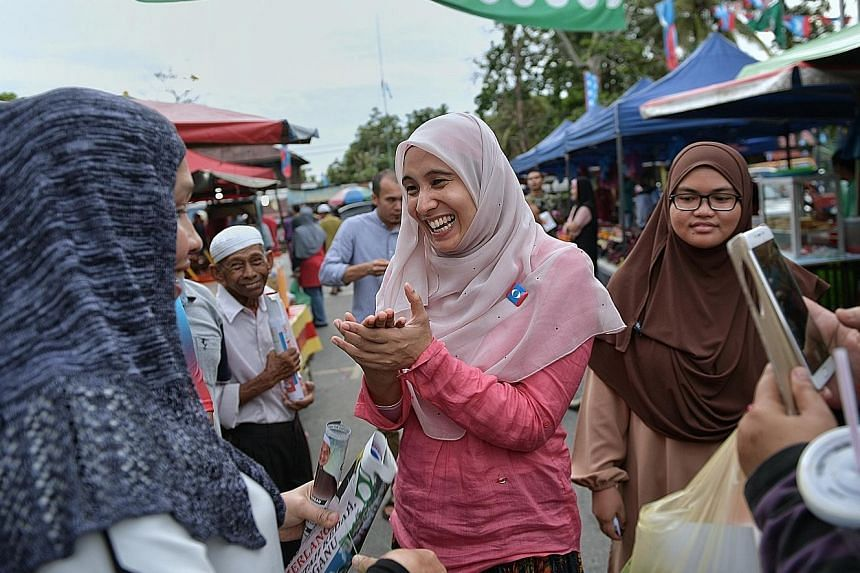 Ms Nurul Izzah Anwar meeting residents at a night market in Permatang Pauh last Tuesday. She is the eldest daughter of jailed opposition leader Anwar Ibrahim and PKR president Wan Azizah Wan Ismail.