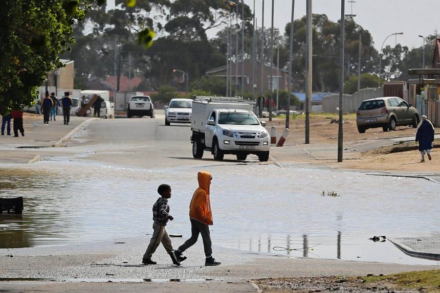 Children walking past a puddle of water after heavy rains in drought-hit Cape Town, South Africa, on April 26, 2018.