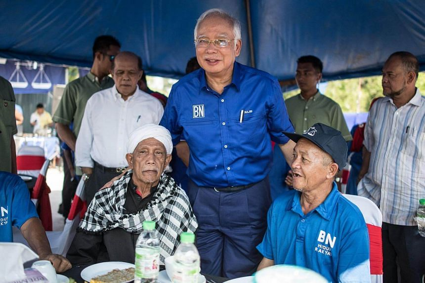 Malaysian PM Najib Razak of the ruling coalition party Barisan Nasional (centre) poses for pictures with his supporters during a campaign event in Pekan, Pahang, on May 6, 2018.