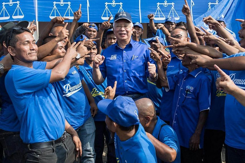 Malaysian PM Najib Razak (centre) poses for pictures with his supporters during a campaign event in Pekan, Pahang, on May 6, 2018.