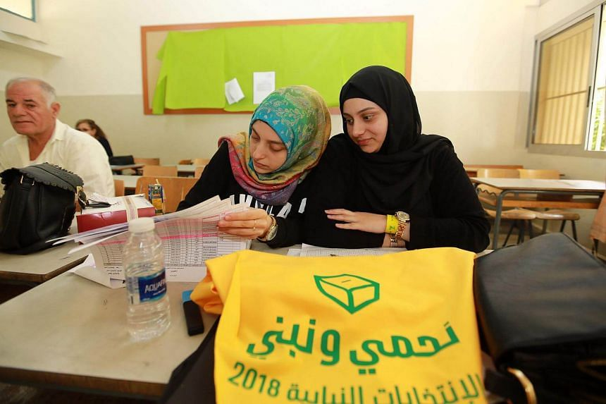 Hizbollah delegates check lists at a polling station in Beirut's southern suburbs, on May 6, 2018.