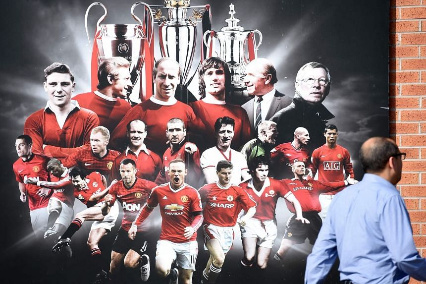 A visitor walking past a billboard featuring the football club's greats, including legendary manager Sir Alex Ferguson (top right), outside the Manchester United Museum at Old Trafford football stadium, Manchester on May 6, 2018.