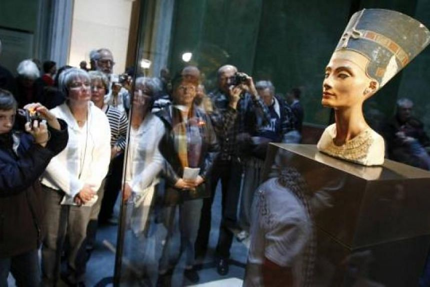 Visitors take pictures of the statue of Nefertiti in the bulletproof display box during the opening for the public at 'Neues Museum' (New Museum) building in Berlin on Oct 17, 2009.