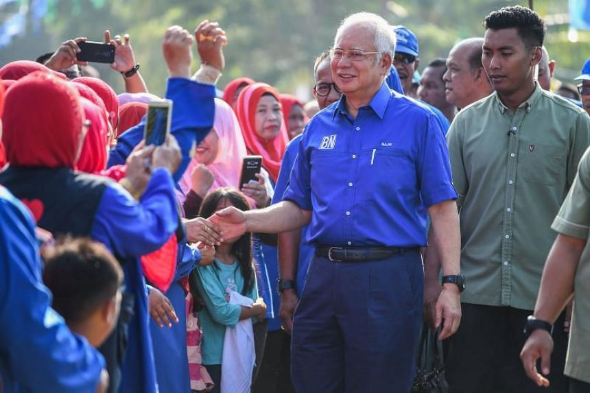 Malaysian Prime Minister Najib Razak of the ruling coalition party Barisan Nasional shakes hands with his supporters during a campaign event in Pekan, Pahang on May 6, 2018.