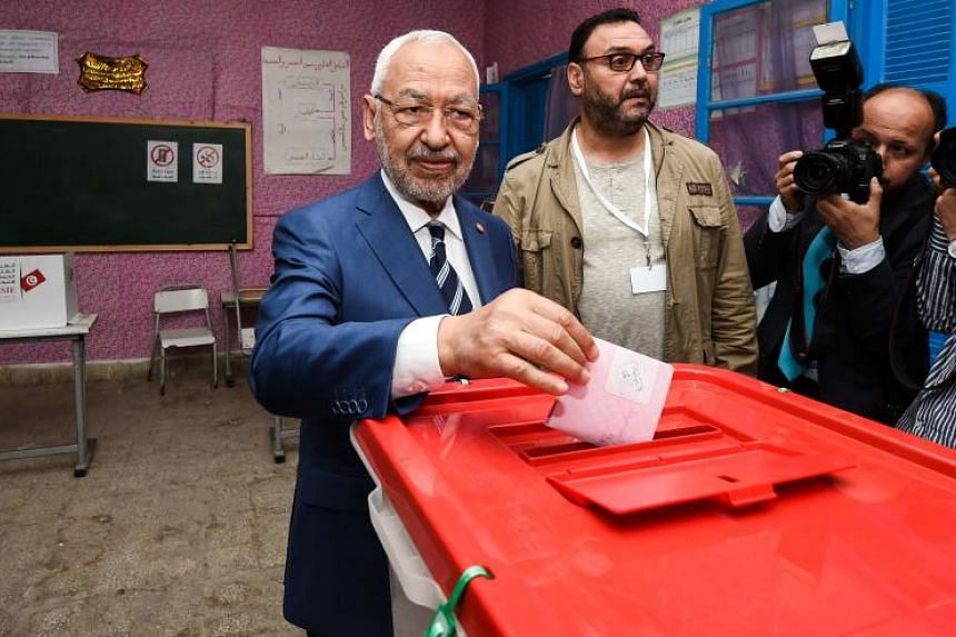 Rached Ghannouchi, leader of the Tunisian Islamist Ennahda party, casts his ballot in a box at a polling station in Ben Arous near the capital Tunis on May 6, 2018, as the country votes in the first free municipal elections since the 2011 revolution.