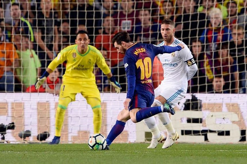 Barcelona's Argentinian forward Lionel Messi (centre) shoots to score a goal during the Spanish league football match between FC Barcelona and Real Madrid CF at the Camp Nou stadium in Barcelona on May 6, 2018.