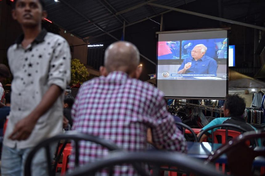 Diners at a coffeeshop along Jalan Raja Bot in Kampung Bahru as Prime Minister Najib Razak gives his interview on TV3 on TV on May 7, 2018.