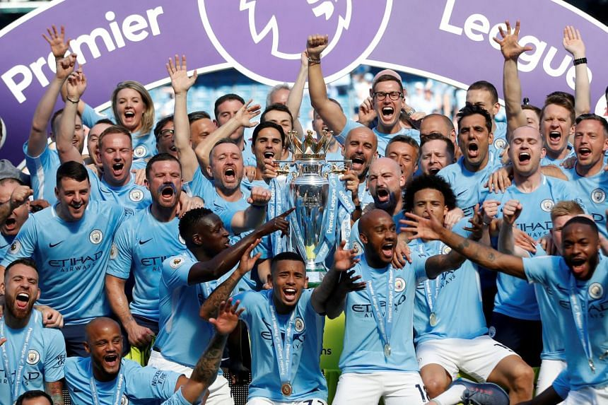 Manchester City celebrate with the trophy after winning the Premier League title.