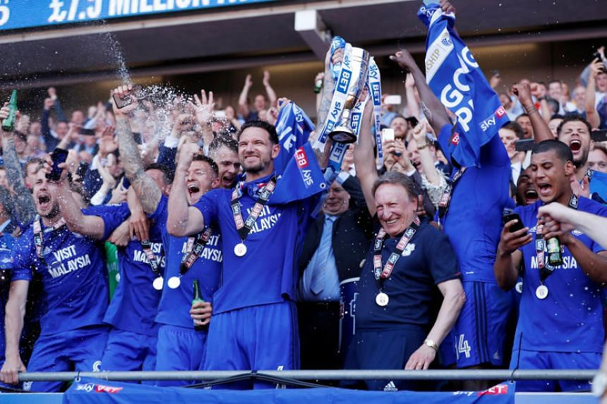 Cardiff City manager Neil Warnock, Gary Madine and team mates lift the trophy as they celebrate promotion to the premier league.