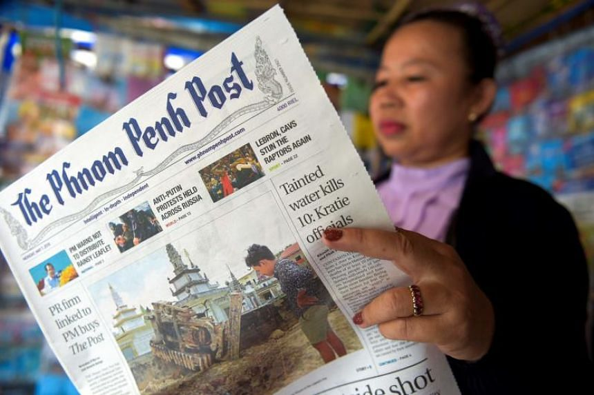 A Cambodian vendor reads the Phnom Penh Post newspaper in Phnom Penh on May 7, 2018.