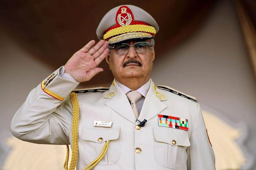 Libyan army commander Khalifa Haftar salutes during a military parade in the eastern city of Bengahzi on May 7, 2018.