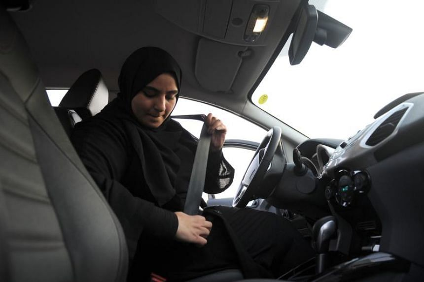 A Saudi woman puts on her seatbelt during a driving lesson in Jeddah on March 7, 2018.