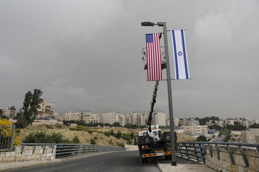 Workers place flags at a road leading to the US consulate in the Jewish neighborhood of Arnona on the East-West Jerusalem line in Jerusalem, Israel, on May 7, 2018.