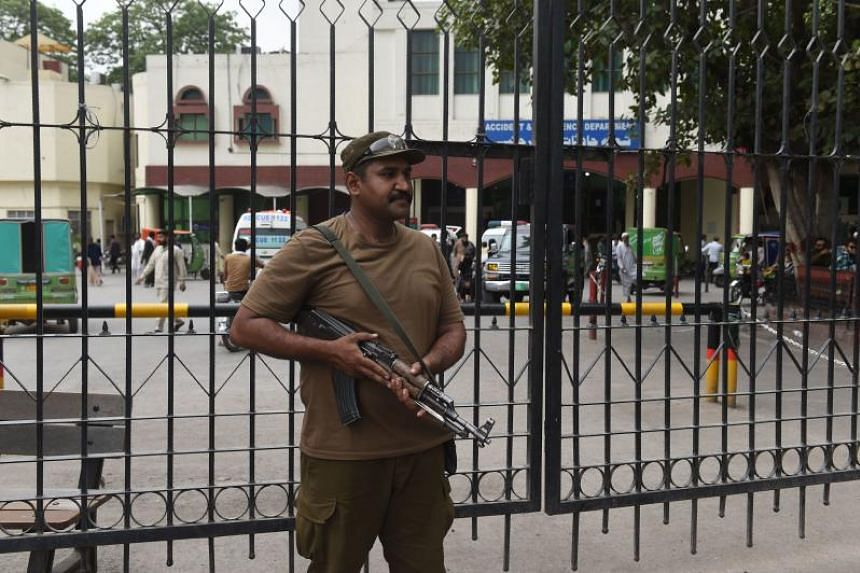 A Pakistani policeman stands guard outside a hospital where country interior minister Ahsan Iqbal shifted after the assassination attempt in Lahore on May 7, 2018.