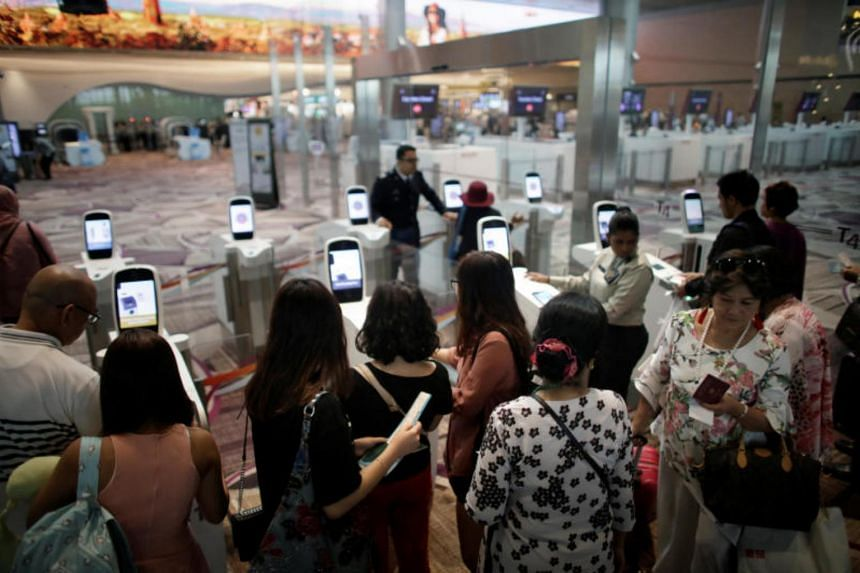 Passengers lining up at automated immigration control gates at Changi airport's Terminal 4 on April 30, 2018.