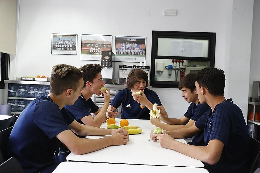 Dario Serra (bottom right) and his VCF Academy team-mates relaxing in one of the rooms at the Ciutat Esportiva. Some 40 trainees who are from outside the city live on campus, with two or three players sharing a room. The live-in VCF Academy players g