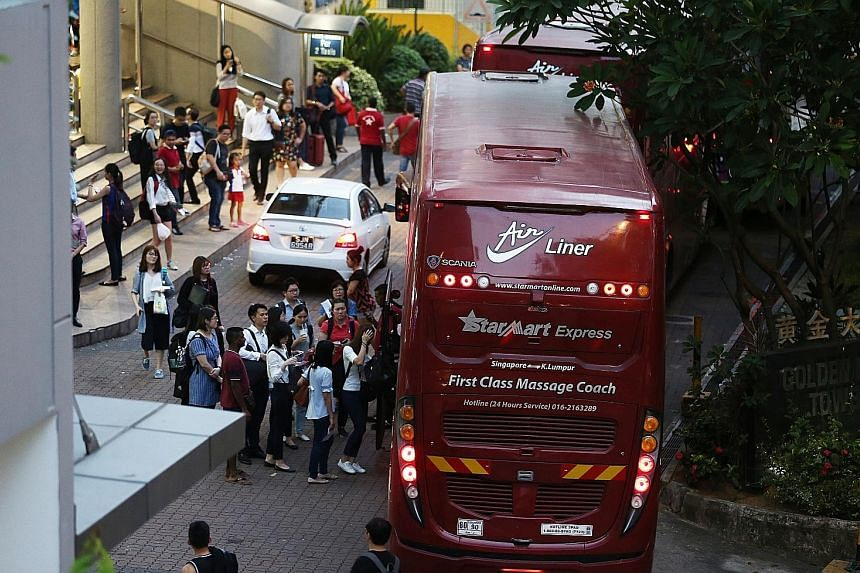 Singapore-based Malaysians boarding coaches at Golden Mile Complex yesterday for the journey home to cast their votes today.